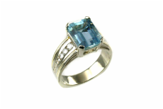 emerald-cut sky blue topaz, custom-designed 14-karat white gold ring with yellow gold braid accents, channel-set diamonds