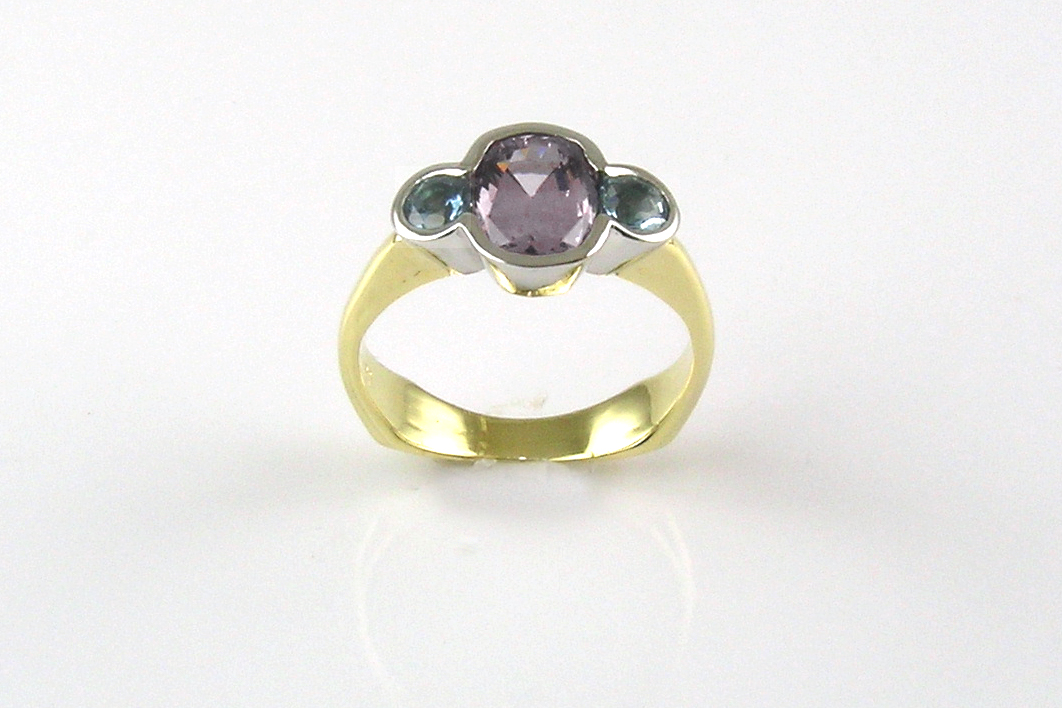 JMD original ring, lavender spinel with teal tourmalines in trio partial bezel with 18-karat yellow gold weighted shank