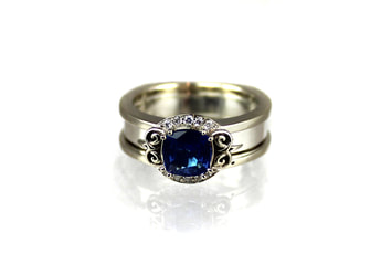 custom-designed sapphire engagement ring, cushion-cut sapphire, reverse-cradle ring, 14-karat white gold, ornate initials on shoulders, partial halo, beadset diamonds