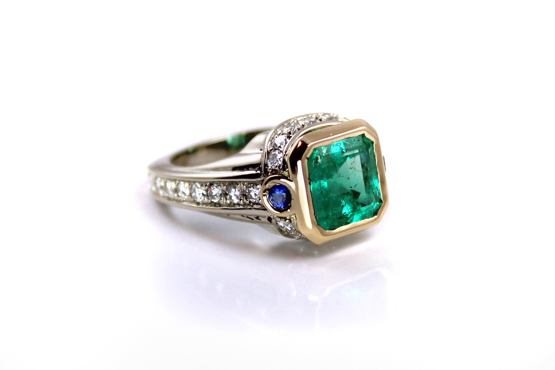 emerald-cut emerald in 18-karat yellow gold bezel, 14-karat white gold ring, custom-designed ring features recycled gemstones and diamonds, beadset diamonds in gallery and shoulders like draped fabric, bezelset sapphires, weighted Euro shank