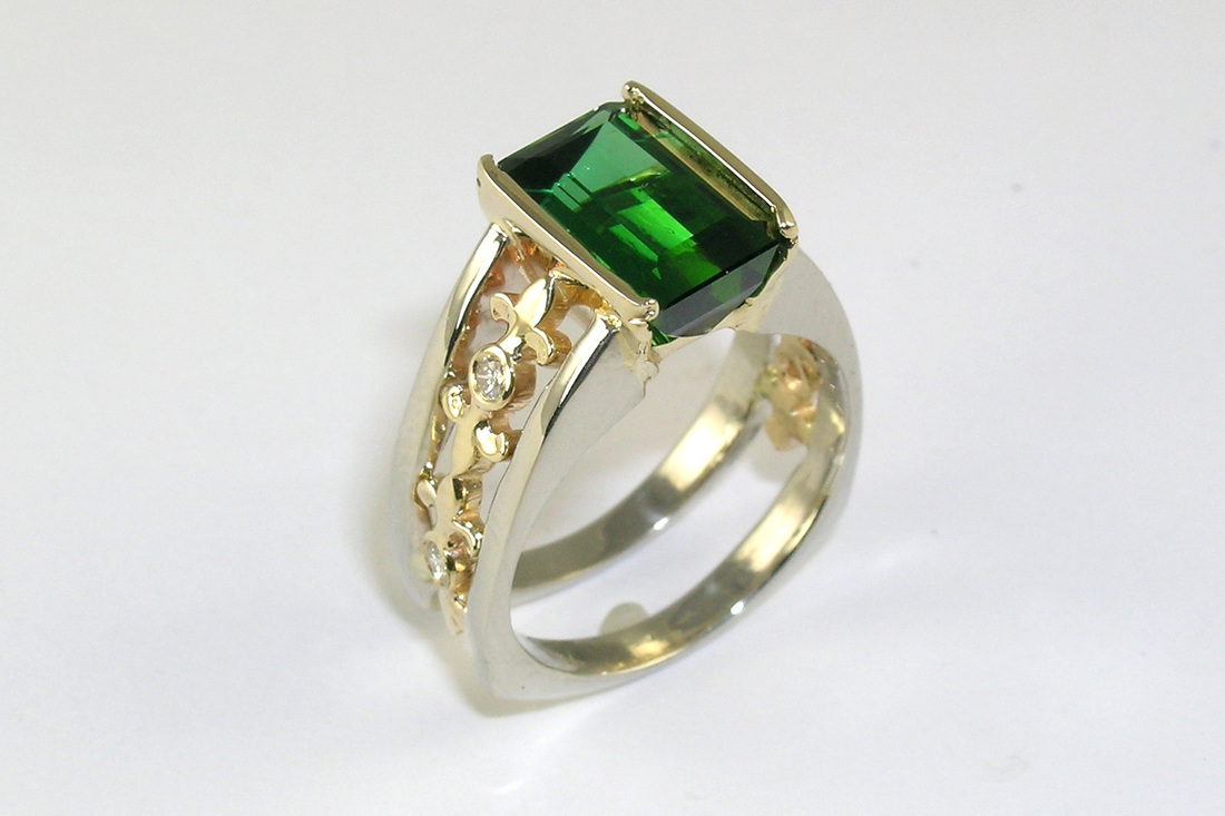 deep green tourmaline, bar-cut gemstone in partial bezel setting, two-tone 14-karat gold ring with fleur de lis design, bezelset diamonds, European shank, open shank design