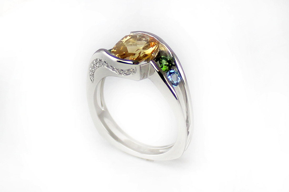 gorgeous yellow topaz in custom-designed mother's ring, birthstones tourmaline and aquamarine in angled channel setting, beadset diamonds swept in curve on thru-finger view, squared Euro shank, open shoulders and partial bezel