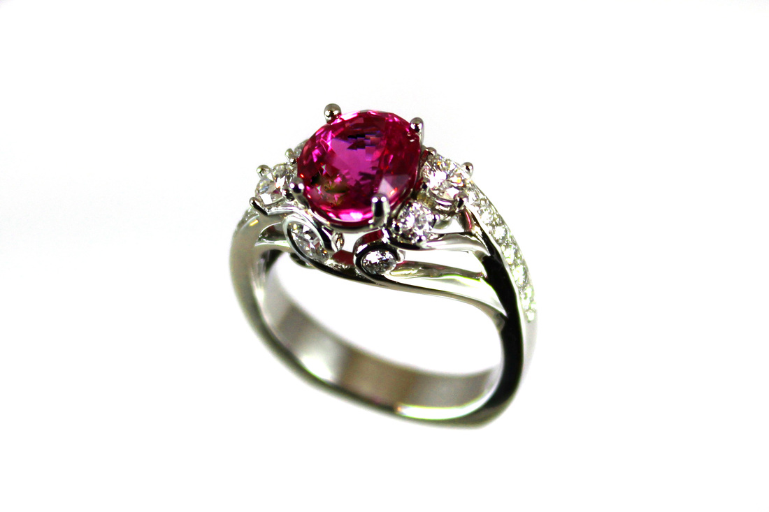 hot pink sapphire in custom platinum ring, intricate scrollwork bezelset diamonds, beadset diamonds on shoulders, weighted Euro shank