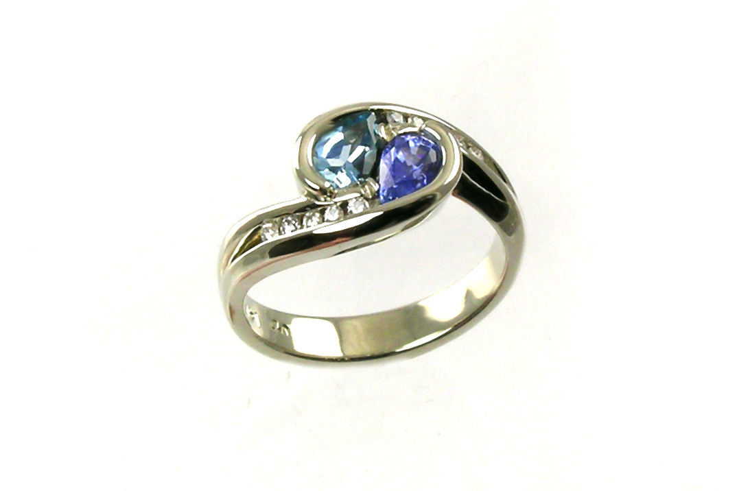 custom-designed engagement ring, 14-karat white gold bypass style with custom-cut pear-shaped aquamarine and purple sapphire, partial bezel set, channel-set diamonds, weighted shank